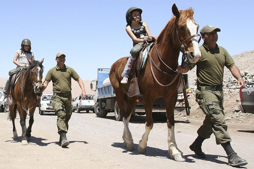 HORSING AROUND: Chilean policemen take the children of trapped miners for a stroll on horseback a few hours before the rescue operation is to begin.
