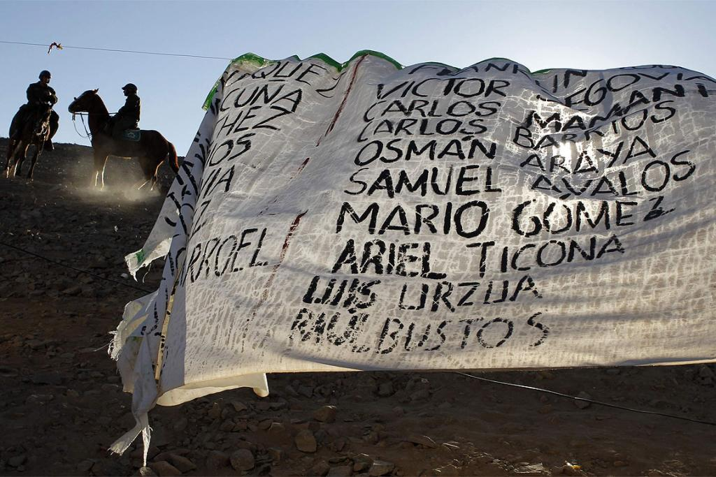 TRIBUTE: Mounted policemen keep journalists off the hills surrounding the area where the operation to rescue the 33 miners trapped underground in the San Jose mine is being prepared. The banner shows the names of the miners.