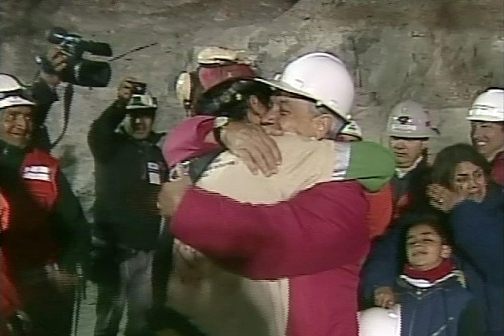 FORTUNATE SON:  Florencio Avalos, the first of 33 workers trapped for more than two months in a Chilean mine, being hugged by Chilean President Sebastian Pinera as wife Monica and son Iaino look on.