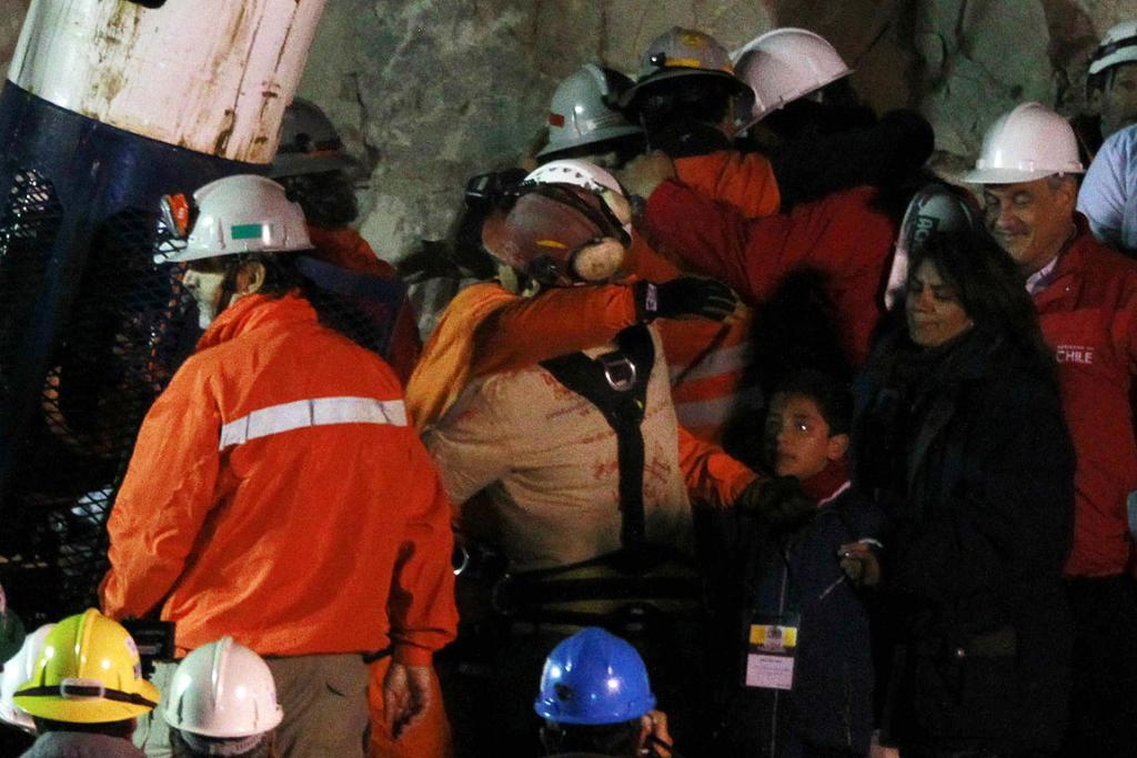 LOOKING UP: Chilean miner Florencio Avalos is embraced by a rescue worker.