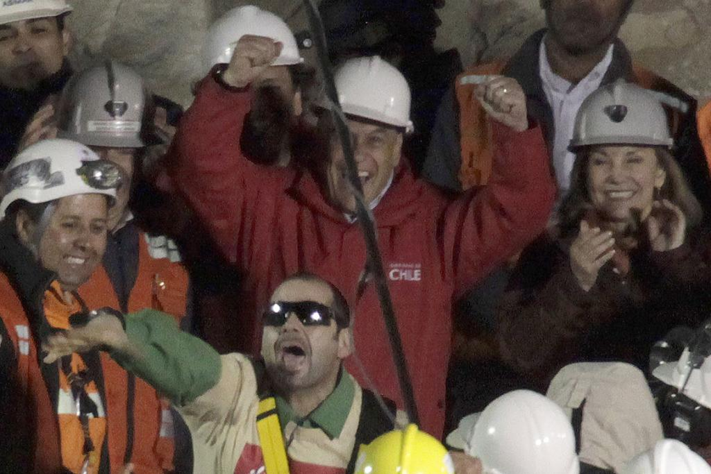 HOLA: Chile's President Sebastian Pinera, center top, cheers as rescued miner Mario Sepulveda Espina, center, salutes after being rescued from the the collapsed San Jose gold and copper mine.
