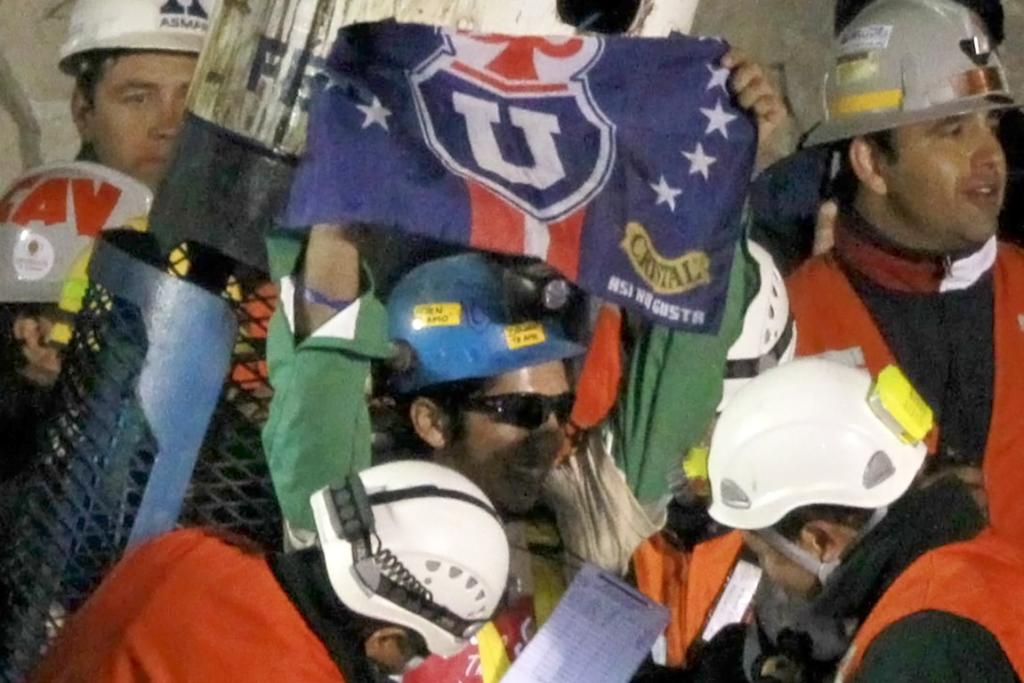 FOOTBALL FAN: Jimmy Sanchez celebrates his freedom from the mine with a flag of his favourite football team.