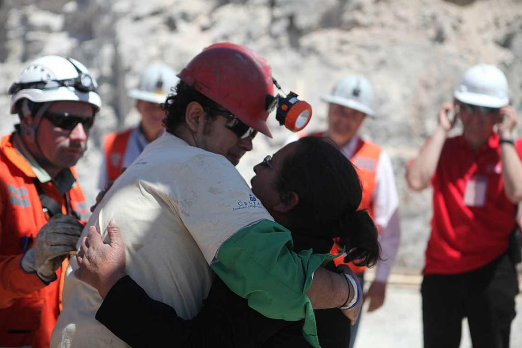 Trapped miner Daniel Herrera (red hard hat) hugs his wife after reaching the surface to become the 16th to be rescued from the San Jose mine in Copiapo.