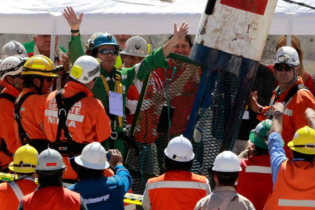 "Trapped miner Pablo Rojas (in green) emerges from the ""Phoenix"" rescue capsule after reaching the surface to become the 19th to be rescued from the San Jose mine."