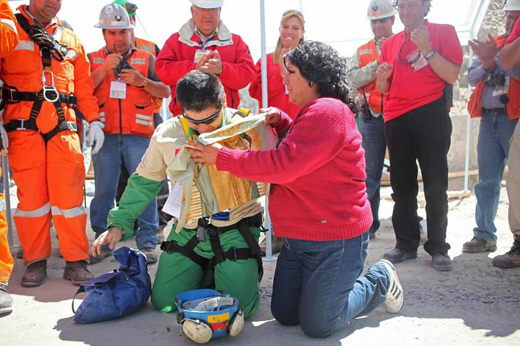 Esteban Rojas kneels to pray as his wife places an image of Our Lady of Guadalupe over him after he reached the surface to became the 18th to be rescued from the San Jose mine.