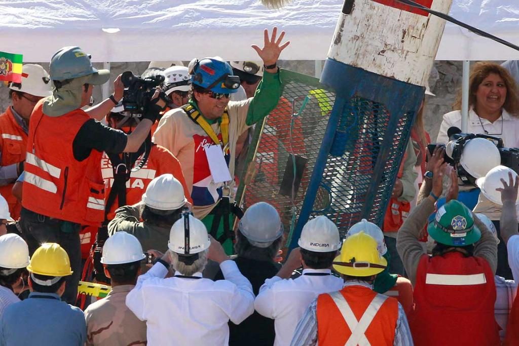 "Trapped miner Samuel Avalos waves as he emerges from the ""Phoenix"" rescue capsule after reaching the surface to become the 22nd person to be rescued."