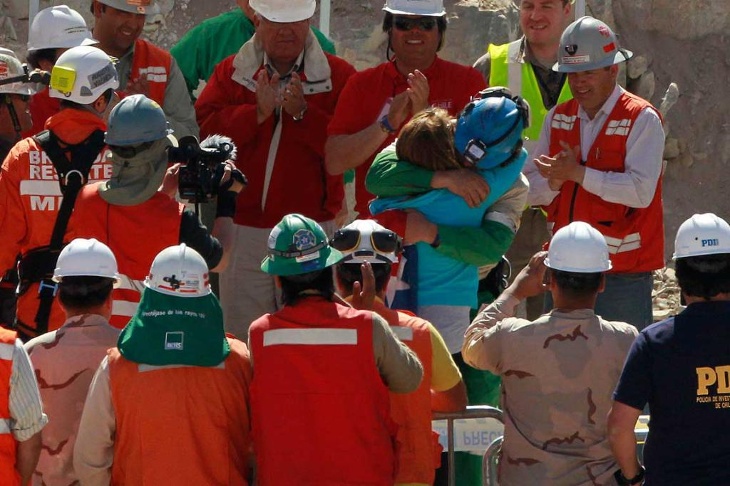 Trapped miner Dario Segovia (blue hard hat) hugs his wife after reaching the surface to become the 20th man to be rescued.