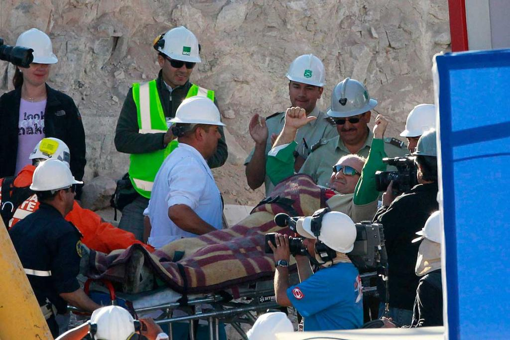 Trapped miner Jose Henriquez is wheeled to a field hospital after reaching the surface to become the 24th to be rescued.