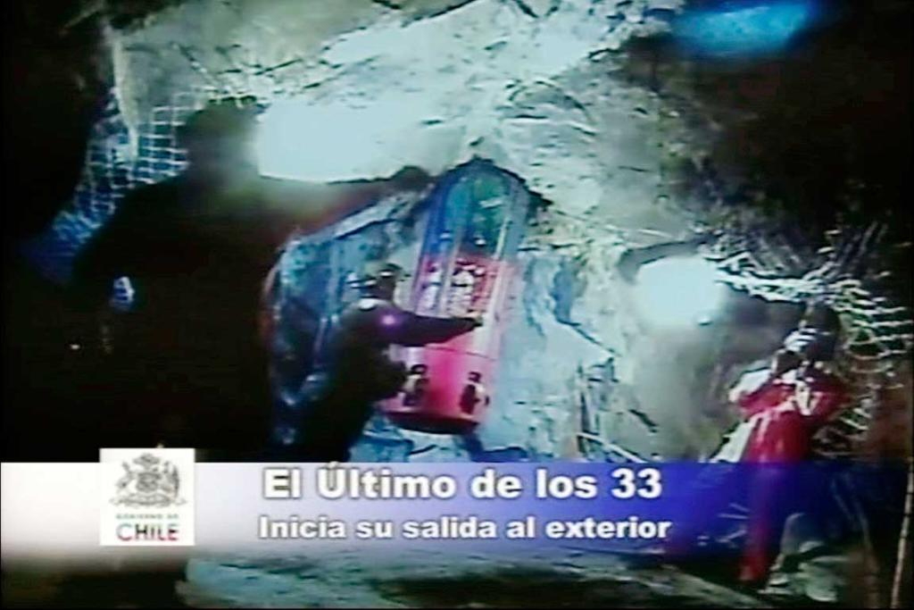A video image taken on October 13, 2010, shows rescuers gesturing as the the Phoenix rescue capsule carrying Luis Urzua, the last of the 33 trapped miners, leave the underground mine.