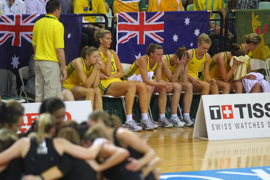 New Zealand players huddle (foreground) while Australians appear shell-shocked after the Silver Ferns won the netball final at the Delhi Commonwealth Games.