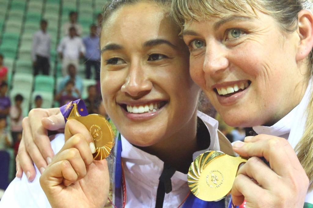 New Zealand players Maria Tutaia and Irene van Dyk show off their gold medals winning the netball final at the Delhi Commonwealth Games.