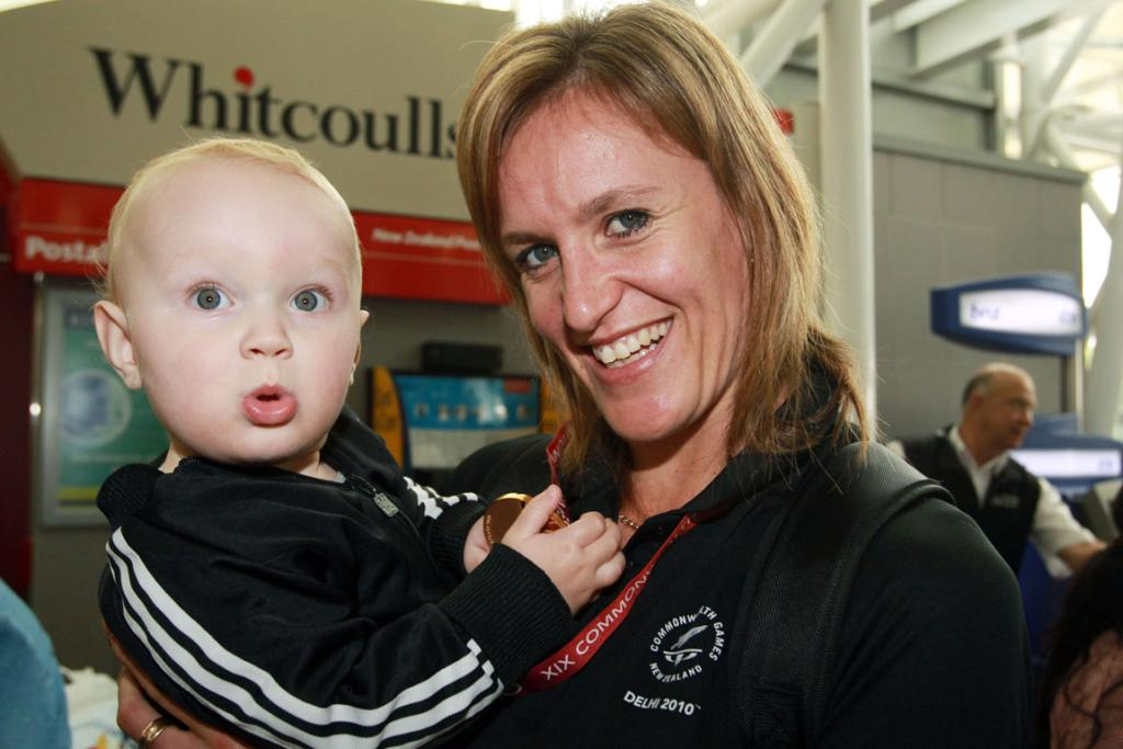 Silver Fern Leanna De Bruin with her son Caleb and her gold medal as Members of the New Zealand Commonwealth Games team arrive home in Auckland.