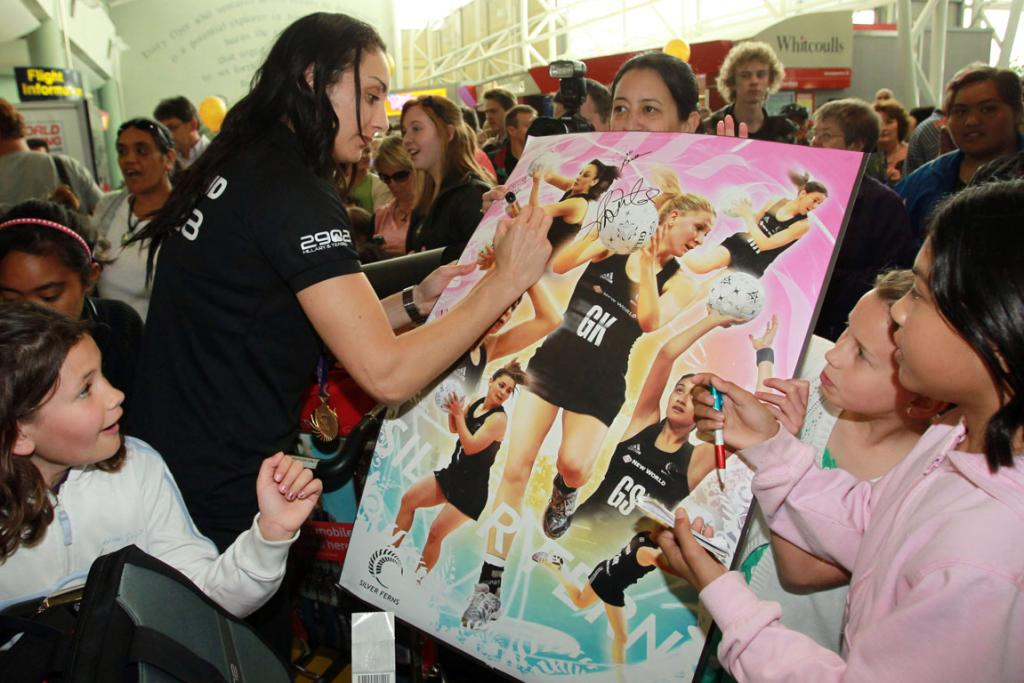 Silver Fern Joline Henry signs her autograph for fans as members of the New Zealand Commonwealth Games team arrive home in Auckland.