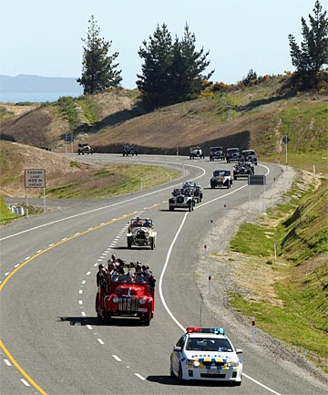 A police car leads a convoy of vintage cars  at the opening of the Ruby Bay bypass.