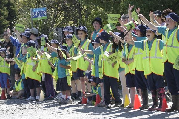 Pupils of Tutarau school cheer on the Tour of Southland as they speed past on Stage three. (Image ID 624857095)