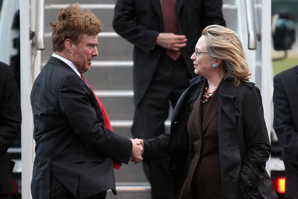 US Secretary of State Hillary Clinton is greeted by US Ambassador David Huebner.