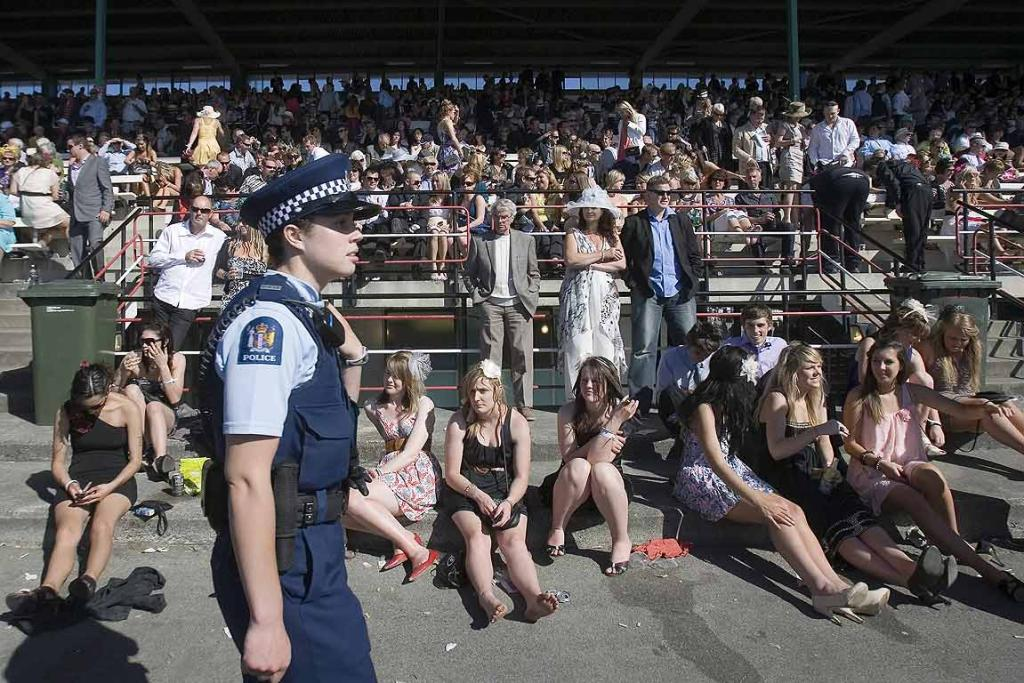 A police officer patrols the public stand area during the NZ Trotting Cup meeting at Addington.