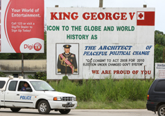 Island-style democracy: A billboard hails the architect of the coming change to the island nation, as a policeman casts an eye on the photographer.