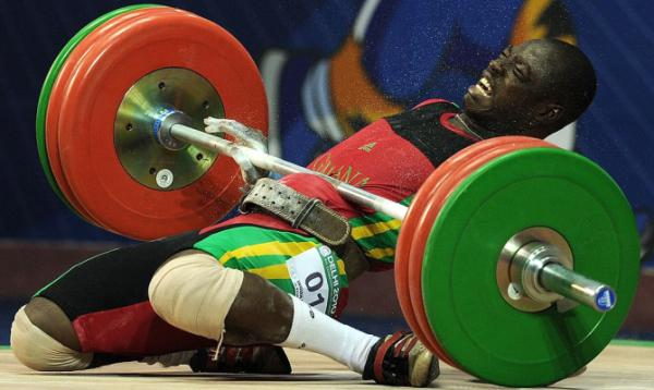 Ghana's Seth Degbe Fetrie falls after he misses a lift during the men's 69kg weightlifting clean and jerk event during the Commonwealth Games at Jawaharlal Nehru sports complex in New Delhi.