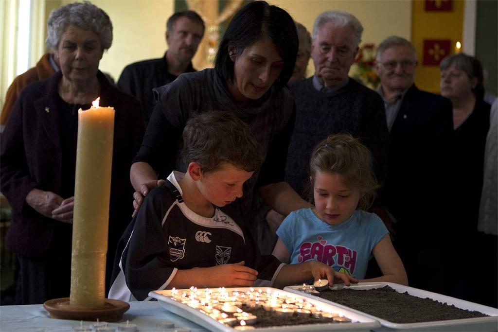 Children at the Holy Trinity Anglican Church in Greymouth light candles for the trapped miners.