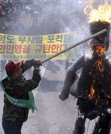 BURNING ISSUE: A member of the Korea Disabled Veterans Organization beats burning effigies of North Korean leader Kim Jong Il and his son Kim Jong Un during a rally denouncing last Tuesday's North Korean bombardment on the South Korean border island of Yeonpyeong.
