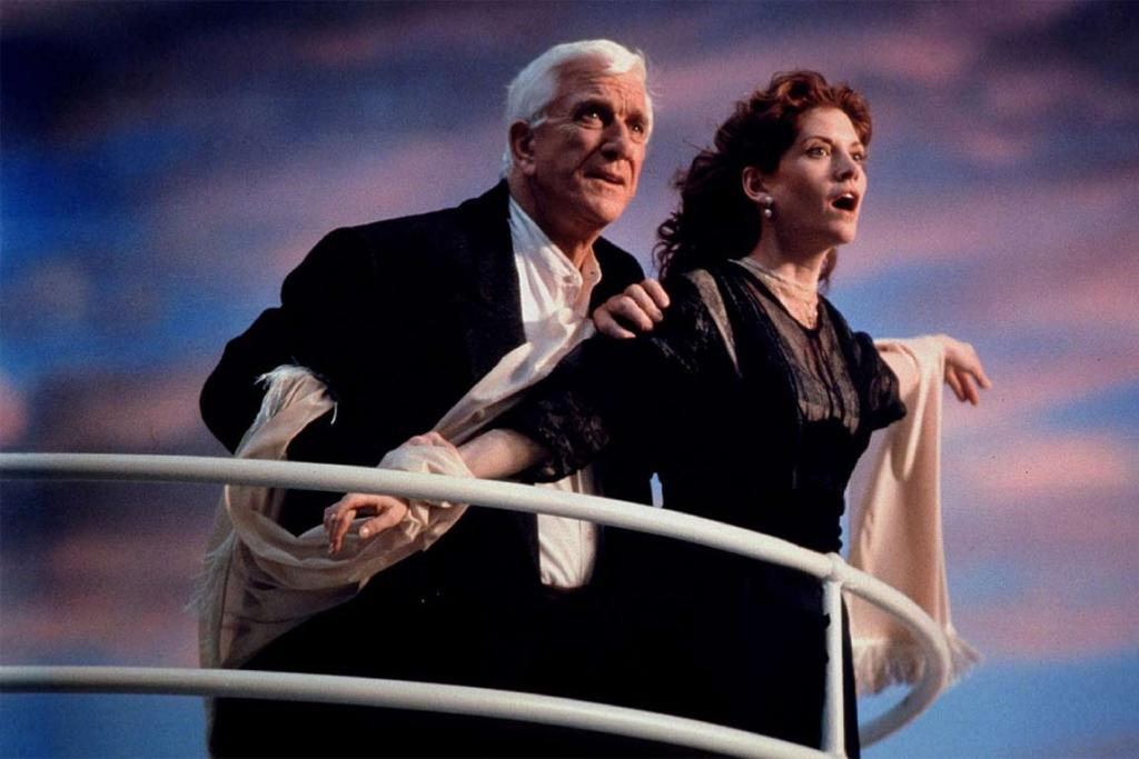 TOP OF THE WORLD: Actors Leslie Nielsen and Melinda McGraw spoofing a scene from Titanic on the set for 1998 film Wrongfully Accused.