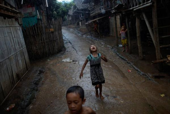 Reuters Images of the Year, photo of girl playing in rain in refugee camp.