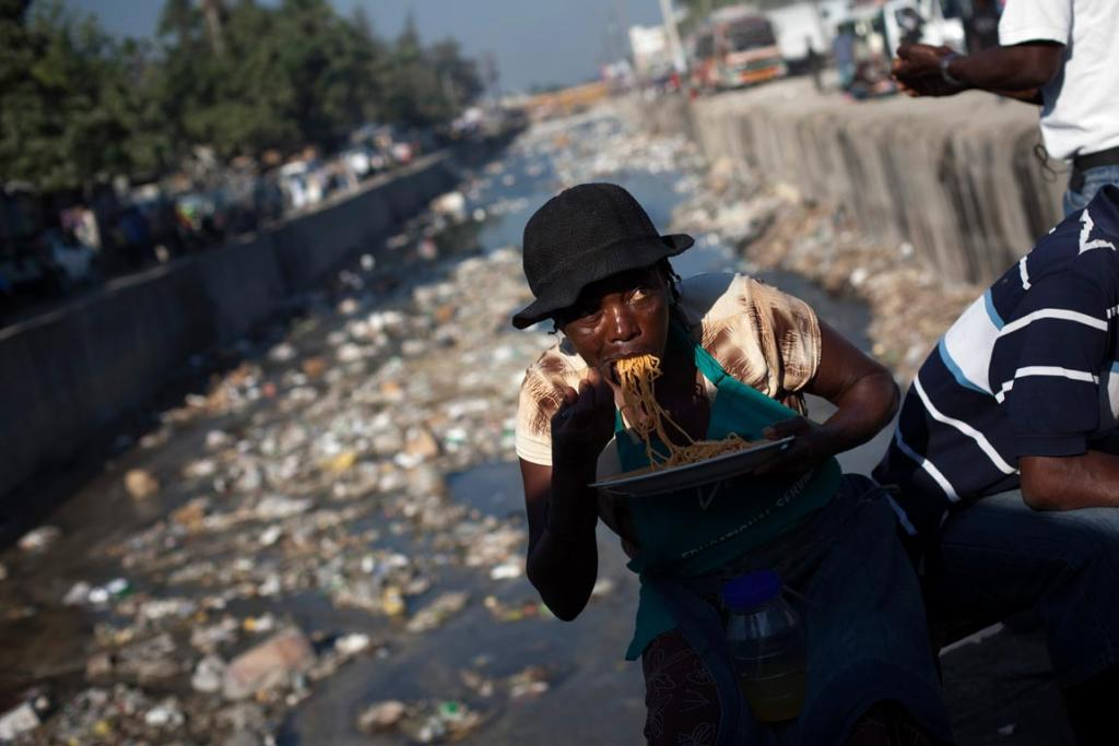 Reuters Images of the Year, photo of woman eating spaghetti on a bridge across a refuse-clogged canal in downtown Port-au-Prince.