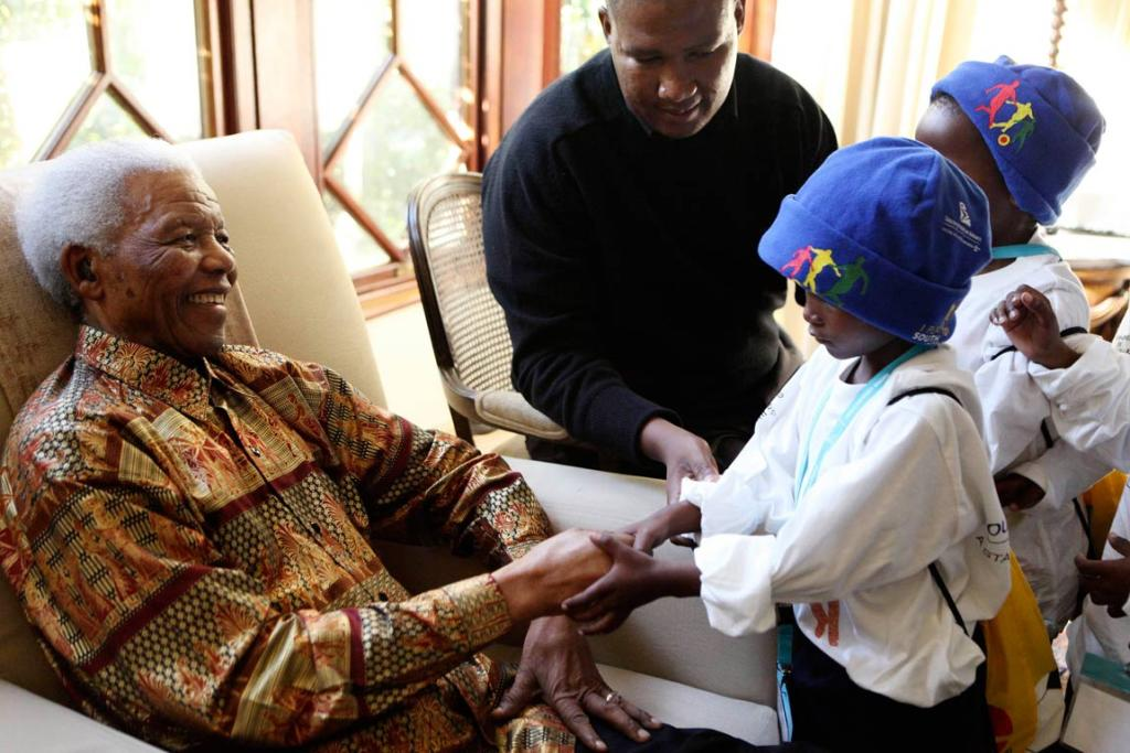 Former President Nelson Mandela greets children from Mvezo and Qunu villages, who came to wish well ahead of his birthday, in Johannesburg in this handout picture released by the Nelson Mandela Foundation on July 17, 2010.
