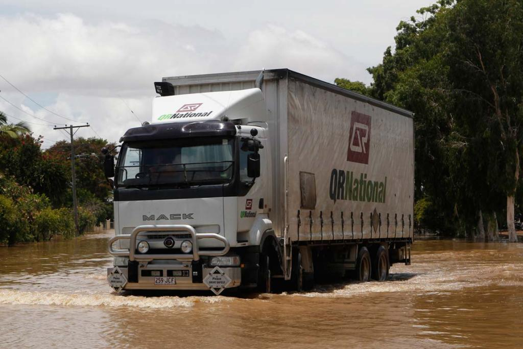 A man drives his truck in floodwaters on a street in Depot Hill in Rockhampton, Queensland.