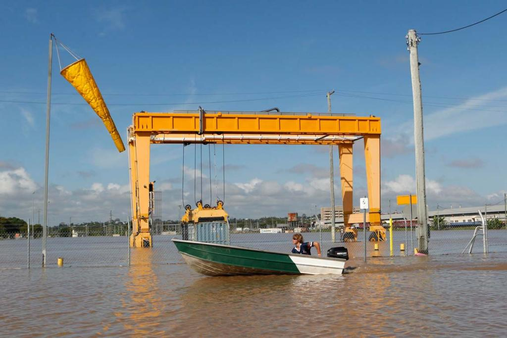 A man rides a boat past a crane partially submerged by floodwaters at a train station in Rockhampton, Queensland.