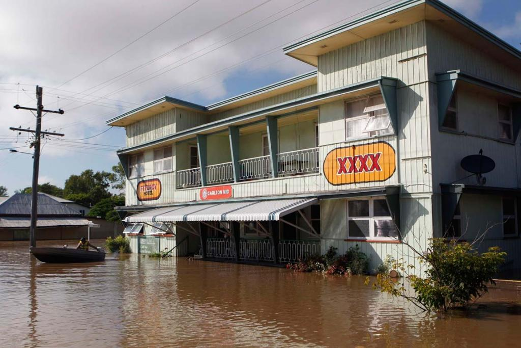 A man leaves the Fitzroy Hotel by boat in flooded Rockhampton, Queensland.