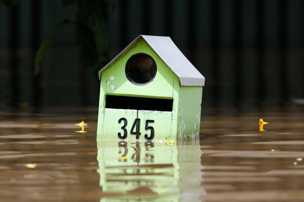 A mailbox is submerged by floodwaters on a street in Rockhampton, Queensland.