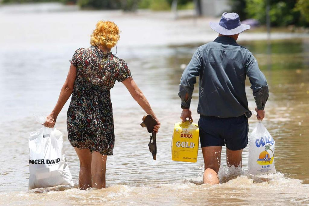 A couple carry the essentials as they walk through floodwaters in Rockhampton, Queensland.
