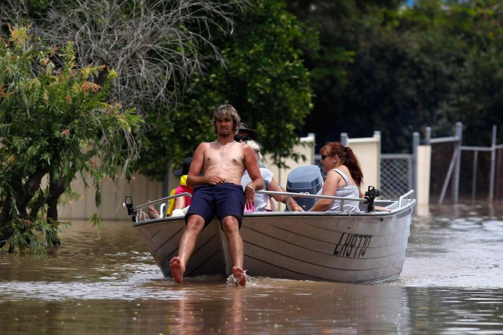 A man sits in the front of his boat as he navigates through floodwaters in Rockhampton, Queensland.