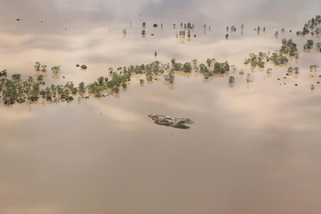 Agricultural machinery on an island created by flood waters near Emerald in Queensland.