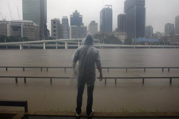 A man looks at the rising Brisbane River in central Brisbane.