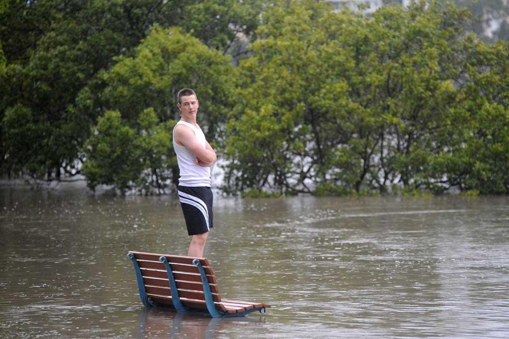 A local looks on as the Brisbane River rises rapidly.