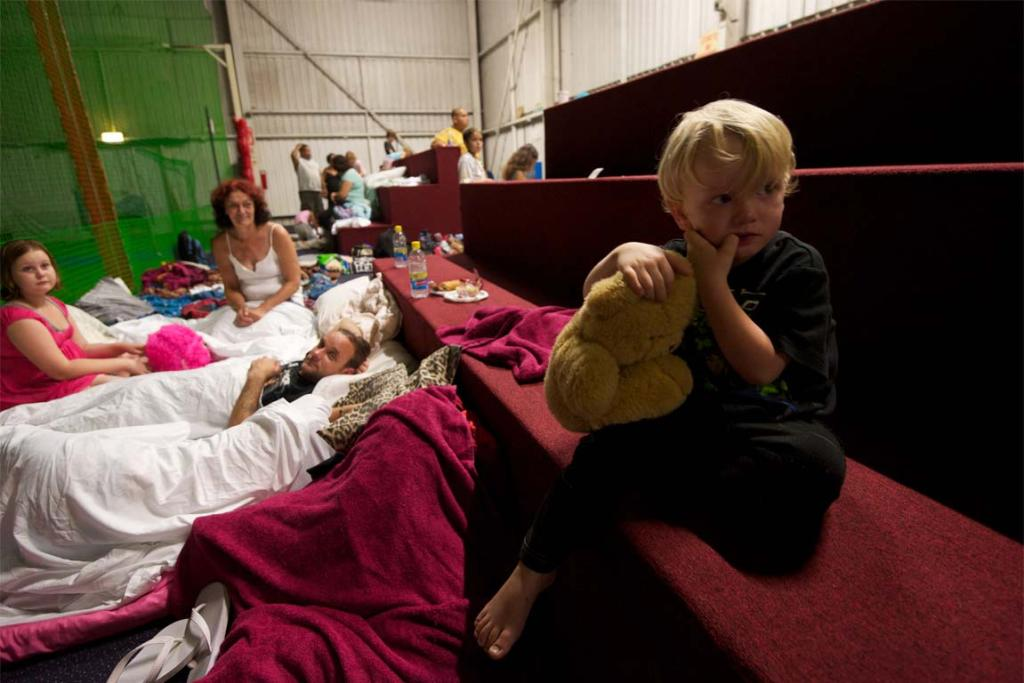 Two-year-old Damien Vieritz gets ready for bed in the evacuation centre at the Ipswich Showgrounds.