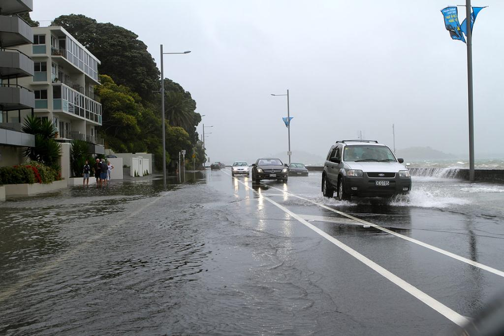 Motorists crawl along a flood Tamaki Drive in Auckland.