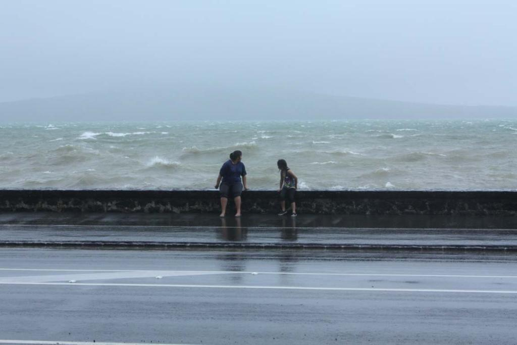 ANTICIPATION: A pair of girls watch the waves on Tamaki Drive in Auckland.