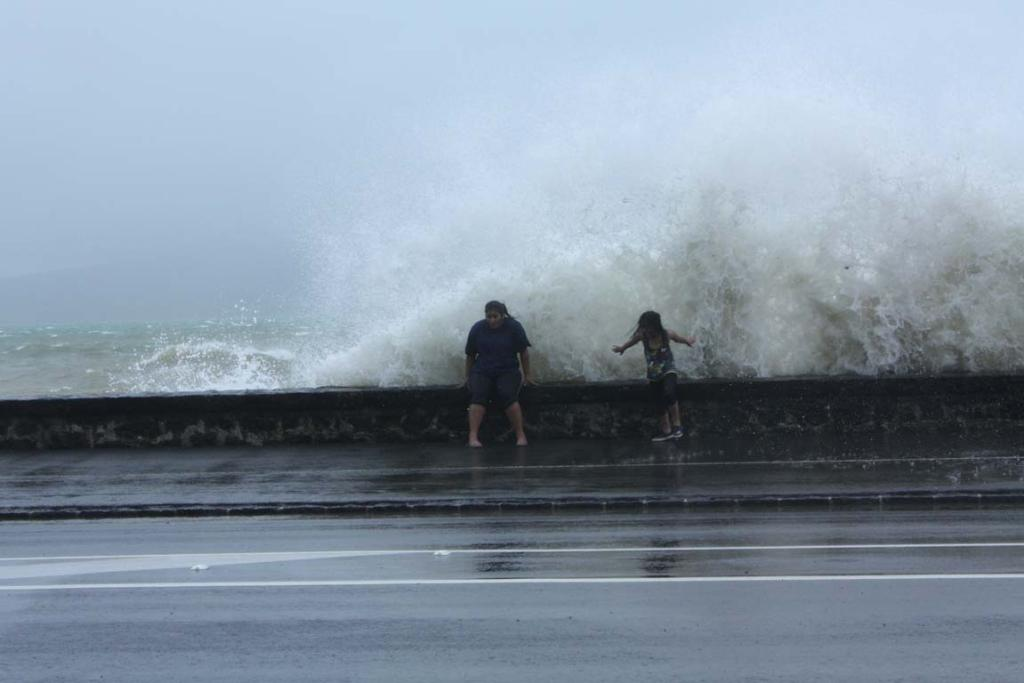 BIG SPLASH: A wave crashes over a pair of girls on Tamaki Drive in Auckland.