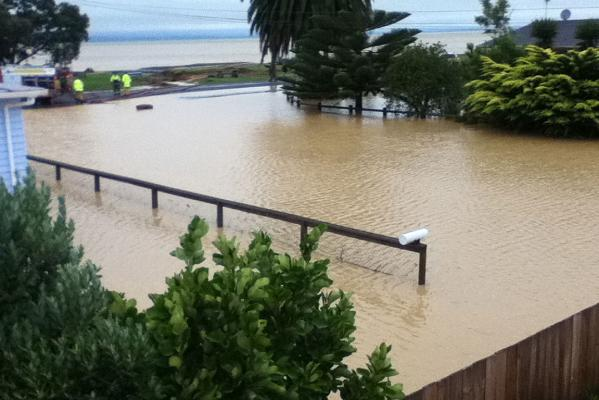 Fire Service staff dig a trench to let floodwaters flow into the sea at Kaiaua.