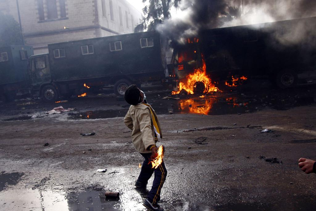 An Egyptian demonstrator throws a fuel bomb at anti-riot police vehicles in the northern city of Suez.