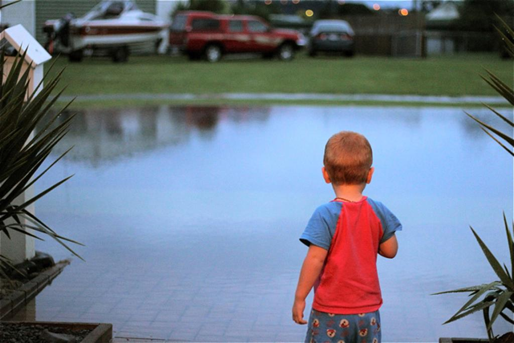 A youngster looks at a flooded street in central Whitianga.