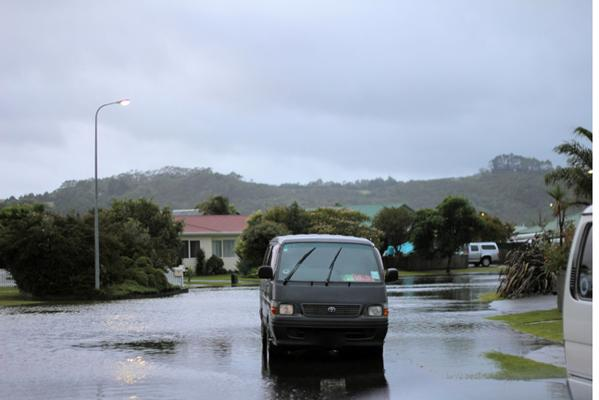 A motorist negotiates a flooded street in central Whitianga.