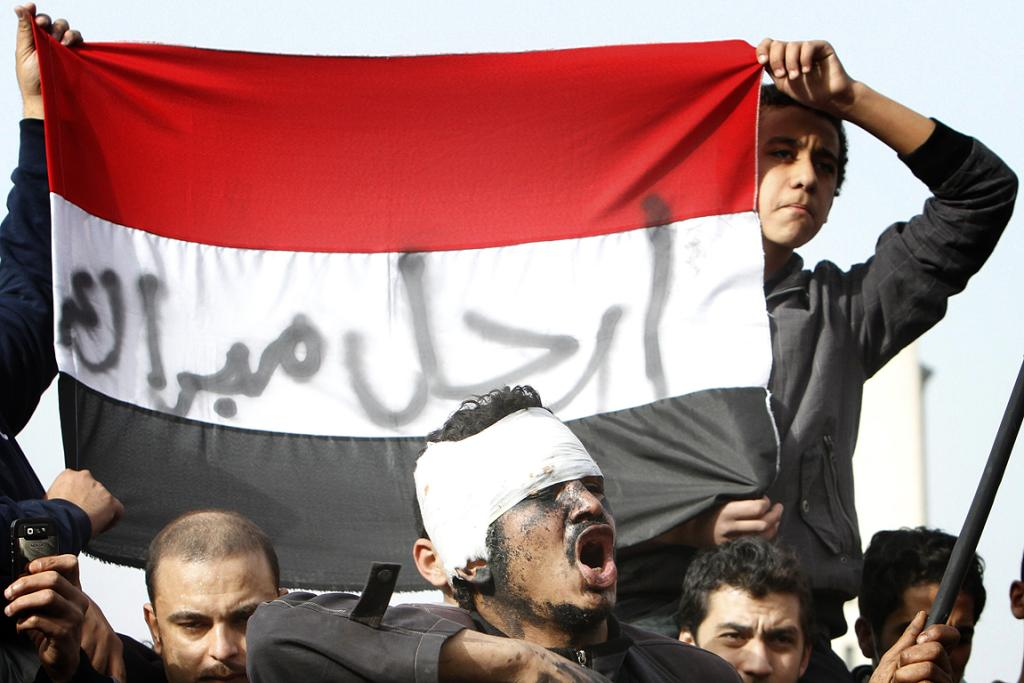 Egyptian protesters hold an Egyptian flag with a slogan reading in Arabic, 'Mubarak go away'.