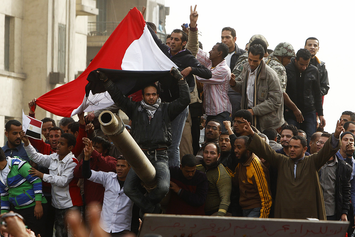 Demonstrators celebrate atop an army tank in Tahrir square during protests in Cairo.