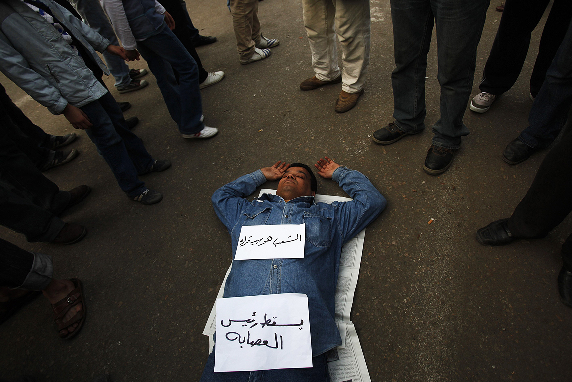 "A protester sleeps at Tahrir Square in Cairo. The banners read ""people decide for themselves"" and ""down with the head of the gang""."