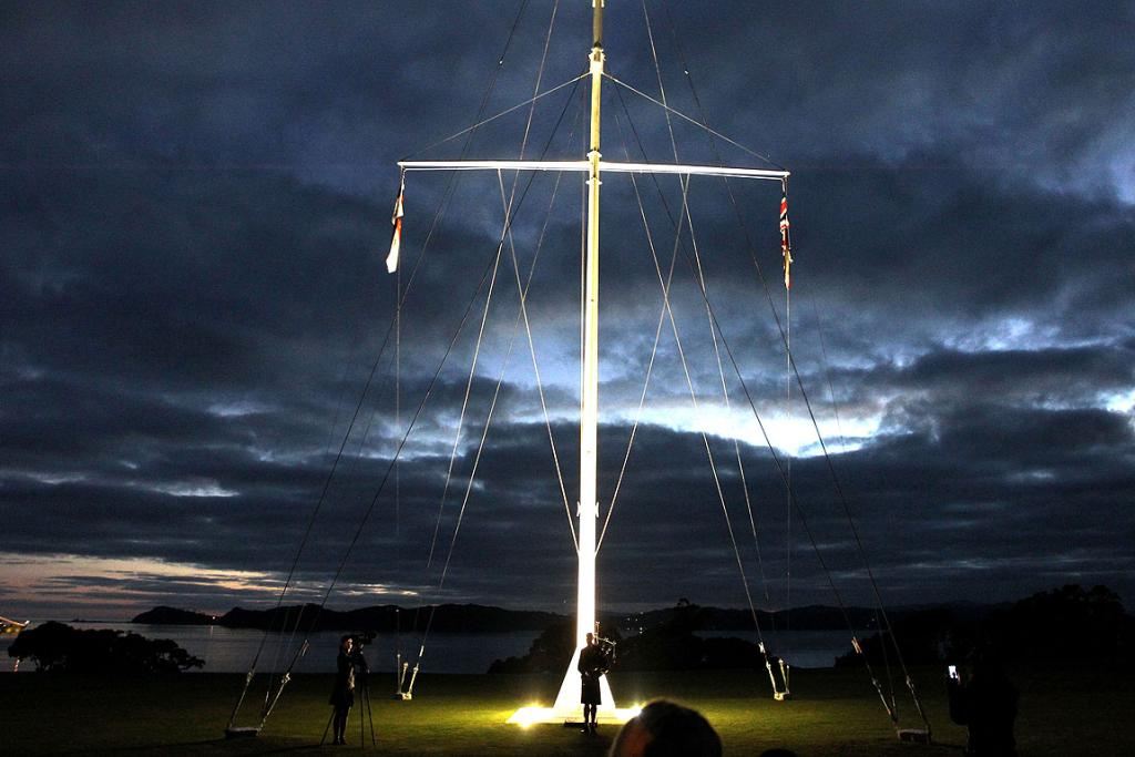 LIT UP: The flagpole is raised at the dawn service on the upper marae at Waitangi.